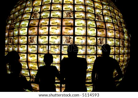 people standing in front of a television cube - stock photo