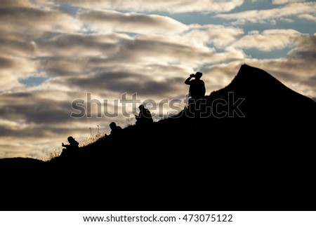 people standing on the top of a hill dmiring the midnight sun at Traena festival 2016, Norway