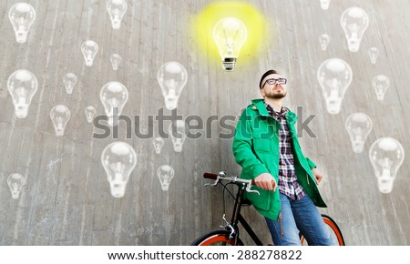 people, startup, inspiration and lifestyle - happy young hipster man with fixed gear bike on city street over concrete wall and lighting bulbs background - stock photo