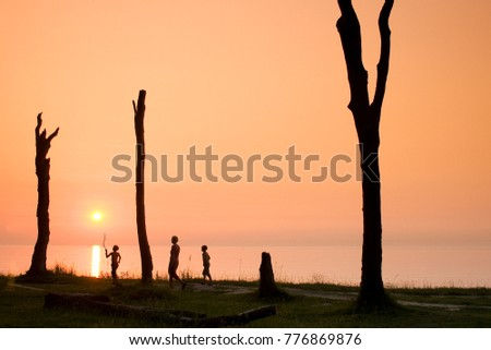 People stroll on the Coastline in Sunset