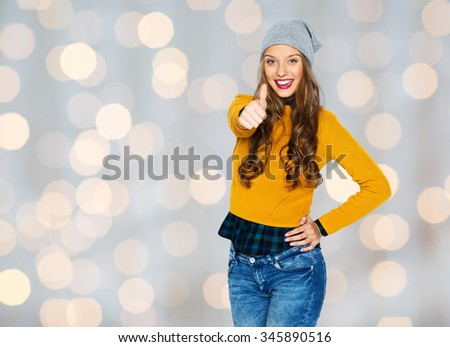 people, style and fashion concept - happy young woman or teen girl in casual clothes and hipster hat showing thumbs up over holidays lights background - stock photo