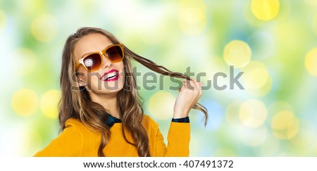 people, style and fashion concept - happy young woman or teen girl in casual clothes and sunglasses over summer green lights background - stock photo