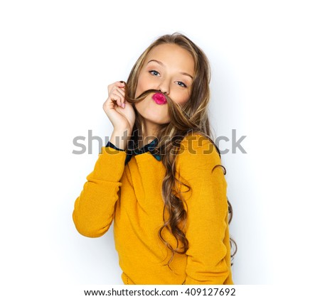 people, style and fashion concept - happy young woman or teen girl in casual clothes having fun making mustache of her hair strand - stock photo