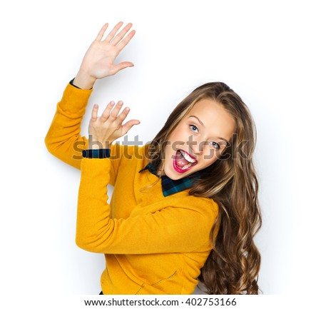 people, style and fashion concept - happy young woman or teen girl in casual clothes having fun and applauding - stock photo