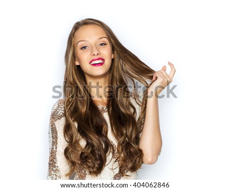 people, style, holidays, hairstyle and fashion concept - happy young woman or teen girl in fancy dress with sequins touching long wavy hair - stock photo