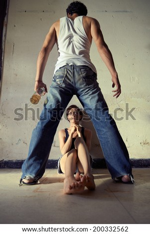 People, substance abuse and domestic violence. Drunk man standing with whiskey bottle and threatening his young wife at home - stock photo