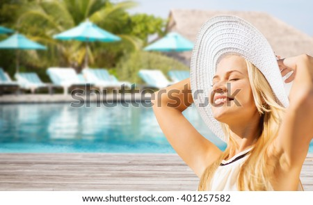 people, summer holidays, travel, tourism and vacation concept - beautiful woman in sun hat enjoying summer over exotic hotel resort beach with swimming pool and sunbeds background - stock photo