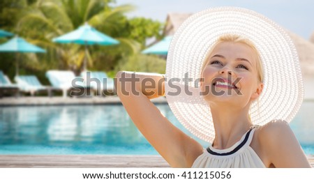 people, summer holidays, travel, tourism and vacation concept - beautiful woman in sun hat enjoying summer outdoors over exotic hotel resort beach with swimming pool and sunbeds background - stock photo