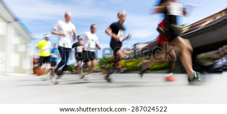 People taking part in running competition in city on bright summer day - stock photo