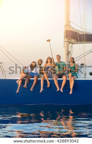 People taking selfies on yacht. Smiling men and women. Weekend with friends. Living the dream. - stock photo