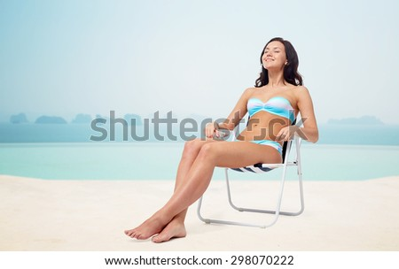 people, tanning, summer and beach concept - happy young woman in bikini swimsuit sunbathing on folding chair over infinity edge pool at hotel resort background