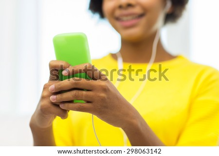 people, technology and leisure concept - close up of happy african american young woman sitting on sofa with smartphone and headphones listening to music at home - stock photo