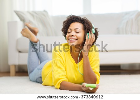 people, technology and leisure concept - happy african american young woman lying on floor with smartphone and headphones listening to music at home - stock photo