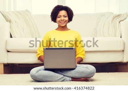 people, technology and leisure concept - happy african american young woman sitting on floor with laptop computer at home