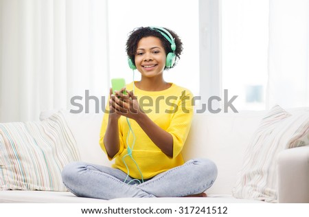 people, technology and leisure concept - happy african american young woman sitting on sofa with smartphone and headphones listening to music at home - stock photo