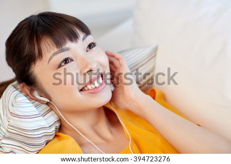 people, technology and leisure concept - happy asian young woman lying on sofa with earphones listening to music at home
