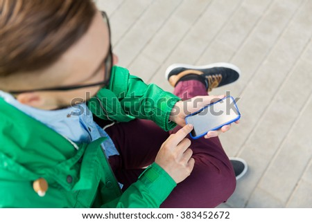 people, technology and lifestyle - close up of young hipster man with smartphone and sitting on street bench in city