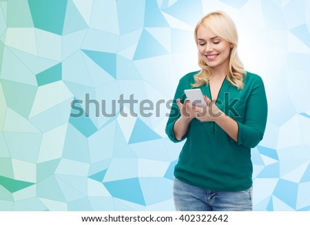 people, technology, communication and leisure concept - happy young woman with smartphone texting message over blue low poly background - stock photo