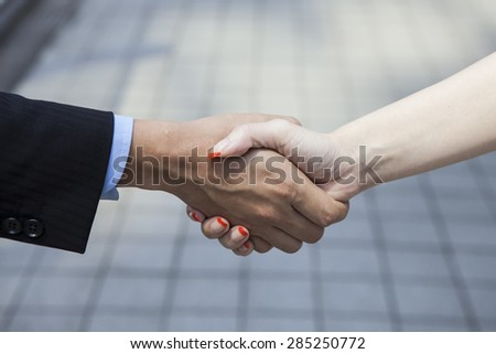 People to shake hands in the office district - stock photo