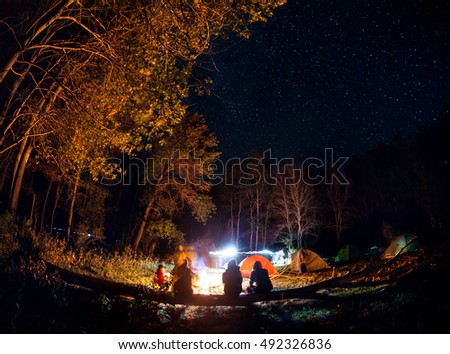 People tourist at Camp in the forest with bonfire at tent around at night starry sky
