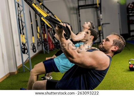 People training body suspension in elastic rope, three strong men
