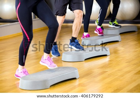 People training with step platform at fitness gym center - stock photo