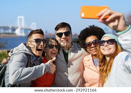 people, travel, tourism, friendship and technology concept - group of happy teenage friends taking selfie with smartphone and showing thumbs up over rainbow bridge at tokyo in japan background - stock photo