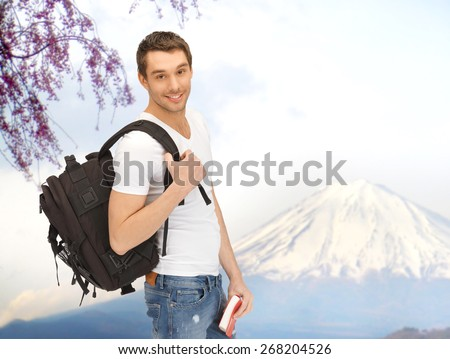 people, travel, tourism, japan and education concept - happy young man with backpack and book traveling over fuji mountain background - stock photo
