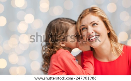 people, trust, love, family and motherhood concept - happy daughter whispering gossip to her mother over holiday lights background - stock photo
