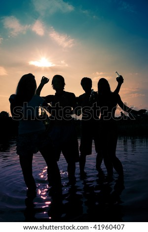People (two couples) on the beach dancing to music, drinking and having a lot of fun in the sunset (only silhouette of people to be seen, people having bottles in their hands)