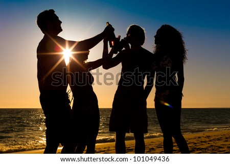 People (two couples) on the beach having a party, drinking and having a lot of fun in the sunset (only silhouette seen, people having bottles in their hands with the sun shining through) - stock photo