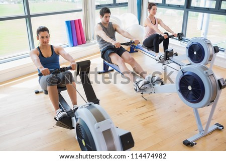 People using rowing machines in fitness studio - stock photo