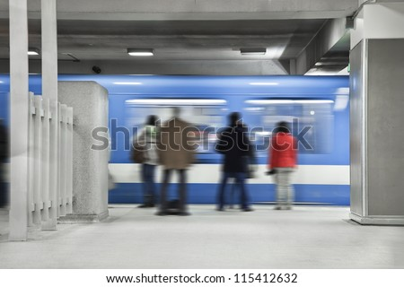 People waiting the next metro. A long exposure of the wagon that show the movements and a blurry people just standing there.Shot during the morning rush hour. - stock photo