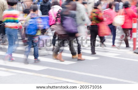 People walk on the zebra crossing to cross the road