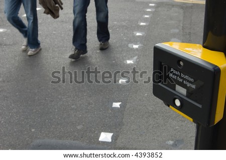 People walking across a pedestrian crossing.  Focus on the crossing sign. - stock photo