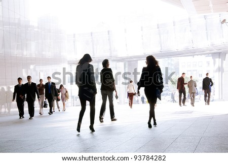 People walking against a light background. - stock photo