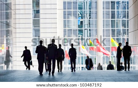 People walking against the light background of an urban landscape. Motion blur. Silhouettes. - stock photo