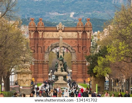 People walking against Triumph Arc in Barcelona, Spain - stock photo