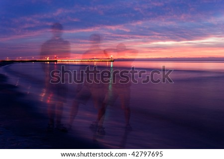 People walking along the beach. Just after sunset. Blur motion. Long exposition.