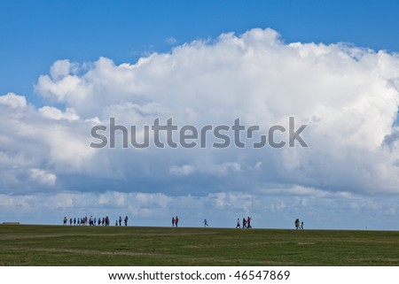 People walking along the horizon with a large cloud overhead