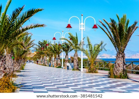 People walking along the seafront palm-lined promenade in Los Arenales del Sol. Costa Blanca, Spain
