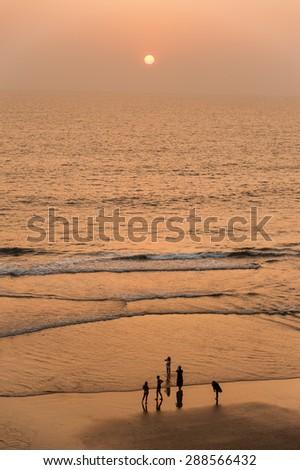 People walking along Varkala beach at sunset. - stock photo