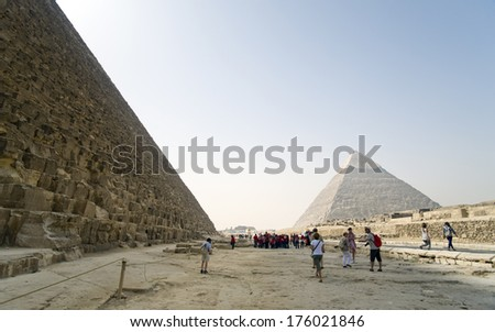 People walking around on a site with Pyramids.