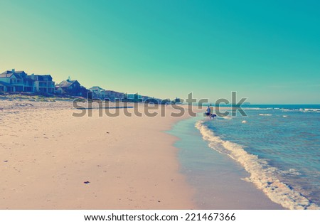 People walking exercising along long sandy beach with retro vintage filter. - stock photo