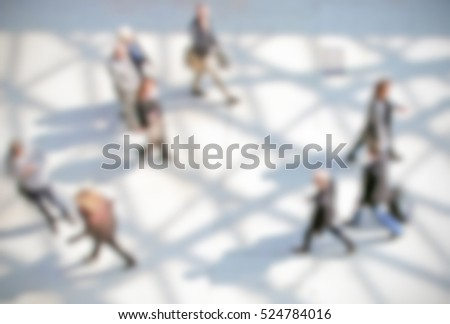 People walking, generic background with an intentional blur effect applied. Humans and location not recognizable.