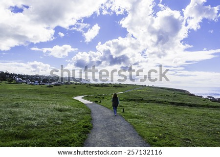 People walking, hiking on a trail, boardwalk, on the Big Sur coast in California. - stock photo