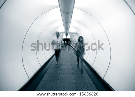 people walking in tunnel in blue doutone - stock photo