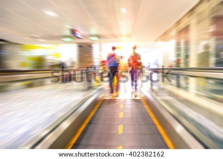 People walking on conveyor belt at international airport  - Man and woman on walkway inside station - Concept of lifestyle and travel with radial zoom defocusing and motion blur effect - stock photo