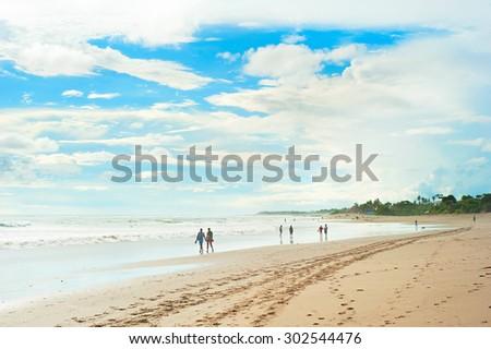 People walking on the beach of Sri Lanka in the sunshine day - stock photo