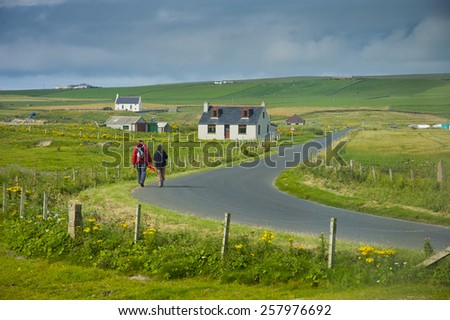 People walking on the road in Scottish landscape in Orkney Island - stock photo